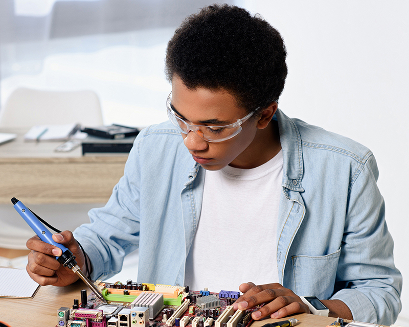 A man soldering a circuit board
